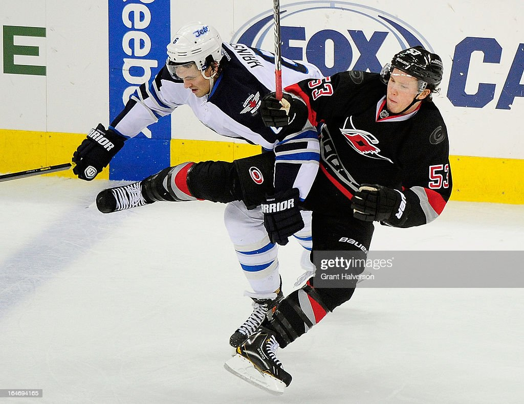 <a gi-track='captionPersonalityLinkClicked' href=/galleries/search?phrase=Ron+Hainsey&family=editorial&specificpeople=206345 ng-click='$event.stopPropagation()'>Ron Hainsey</a> #6 of the Winnipeg Jets makes an open-ice hit on <a gi-track='captionPersonalityLinkClicked' href=/galleries/search?phrase=Jeff+Skinner&family=editorial&specificpeople=3147596 ng-click='$event.stopPropagation()'>Jeff Skinner</a> #53 of the Carolina Hurricanes during play at PNC Arena on March 26, 2013 in Raleigh, North Carolina. Winnipeg won 4-1.