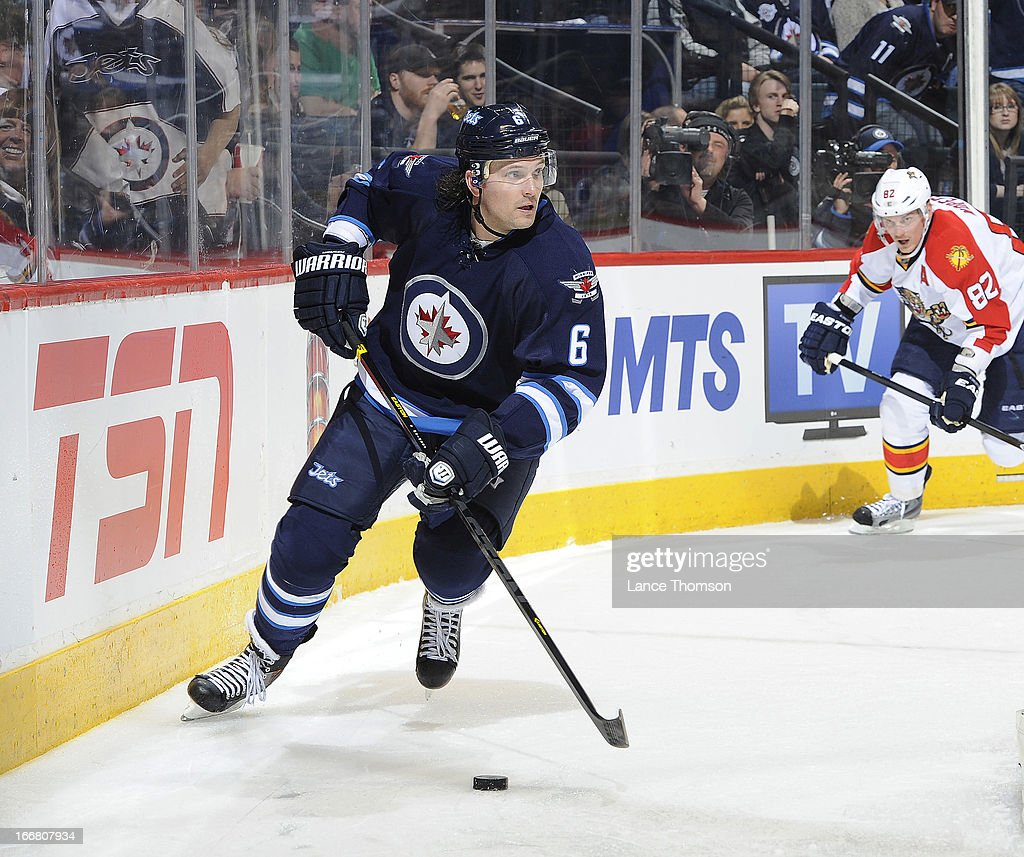 Ron Hainsey #6 of the Winnipeg Jets plays the puck along the boards as Tomas Kopecky #82 of the Florida Panthers gives chase during third period action at the MTS Centre on April 11, 2013 in Winnipeg, Manitoba, Canada. The Jets defeated the Panthers 7-2.