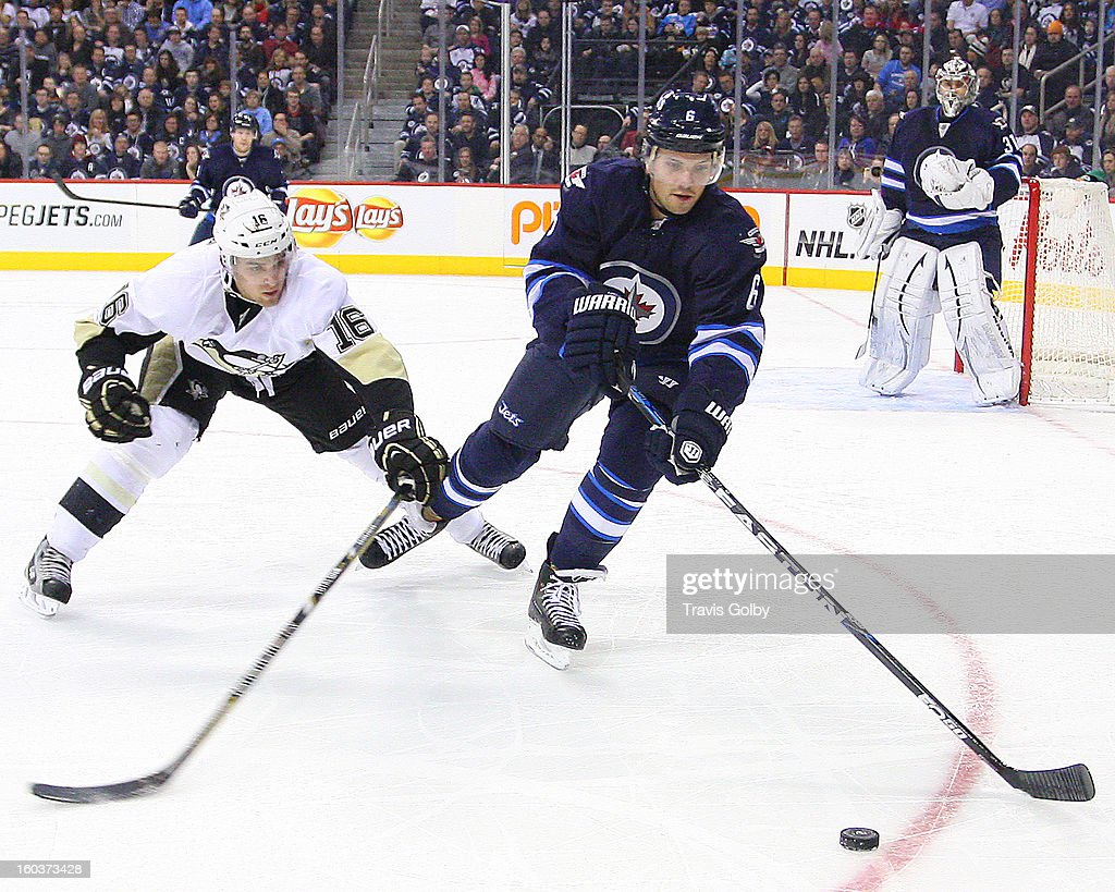 <a gi-track='captionPersonalityLinkClicked' href=/galleries/search?phrase=Ron+Hainsey&family=editorial&specificpeople=206345 ng-click='$event.stopPropagation()'>Ron Hainsey</a> #6 of the Winnipeg Jets reaches out to play the puck away from <a gi-track='captionPersonalityLinkClicked' href=/galleries/search?phrase=Brandon+Sutter&family=editorial&specificpeople=2086411 ng-click='$event.stopPropagation()'>Brandon Sutter</a> #16 of the Pittsburgh Penguins during second period action at the MTS Centre on January 25, 2013 in Winnipeg, Manitoba, Canada. The Jets defeated the Pens 4-2.