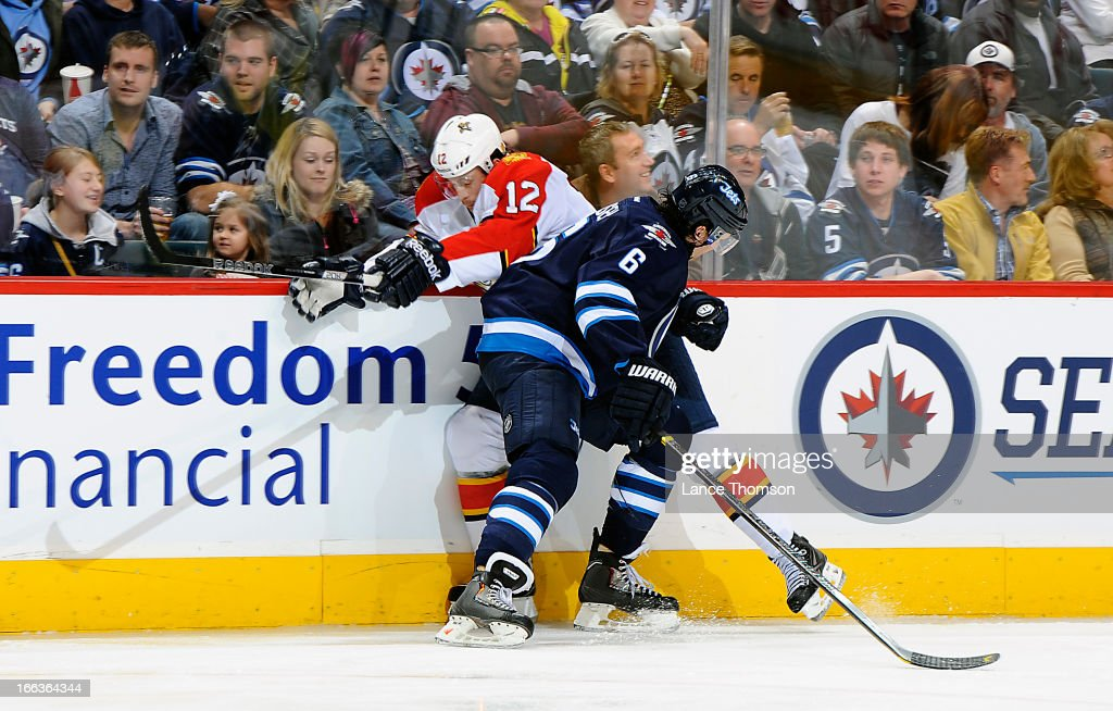 <a gi-track='captionPersonalityLinkClicked' href=/galleries/search?phrase=Ron+Hainsey&family=editorial&specificpeople=206345 ng-click='$event.stopPropagation()'>Ron Hainsey</a> #6 of the Winnipeg Jets rubs out <a gi-track='captionPersonalityLinkClicked' href=/galleries/search?phrase=Jack+Skille&family=editorial&specificpeople=697014 ng-click='$event.stopPropagation()'>Jack Skille</a> #12 of the Florida Panthers along the boards during third period action at the MTS Centre on April 11, 2013 in Winnipeg, Manitoba, Canada.