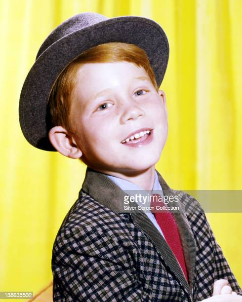 Ron Howard US actor and director wearing a grey hat and checked jacket with a blue shirt and a red tie in a studio portrait issued as publicity for...