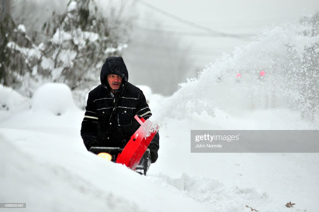 Ron Lelito attempts to remove some of the five feet of snow from a driveway on November 20 2014 in the Lakeview neighborhood of Buffalo New York The...