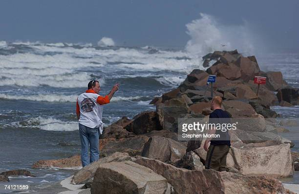 Ron Maco of Jacksonville Florida and David Pritt of Flint Michigan watch waves crash on the jetties at the entrance of the St Johns River from...