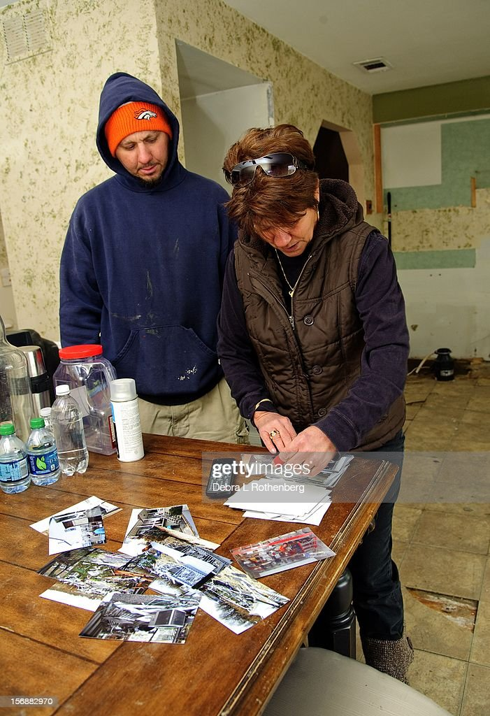 Ron Peperoni Jr. and his mother Joann look at photos that they found amongst the rubble of their house on Front Street on November 16, 2012 in Union Beach, New Jersey. Hurricane Sandy devastated this small waterfront town on October 29, 2012. Residents who lived near the water were allowed back into town 3 days ago, only to find many of their homes are either gone or condemned.