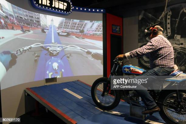 Ron Pope jumps on a motorcycle over a group of police cars via virtual reality at the Evel Knievel Museum in Topeka Kansas on June 21 2017 Step...