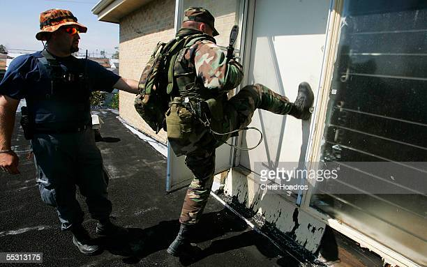 Ron Scott of the Chickasaw Nation Oklahoma Search and Rescue and Staff Sgt Don Davis of the Oklahoma National Guard kick in the door of a house while...