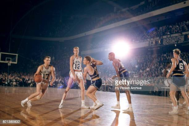 Ron Sobie of the New York Knicks dribbles the ball as his teammate Kenny Sears sets the pick on Jack George of the Philadelphia Warriors as he and...