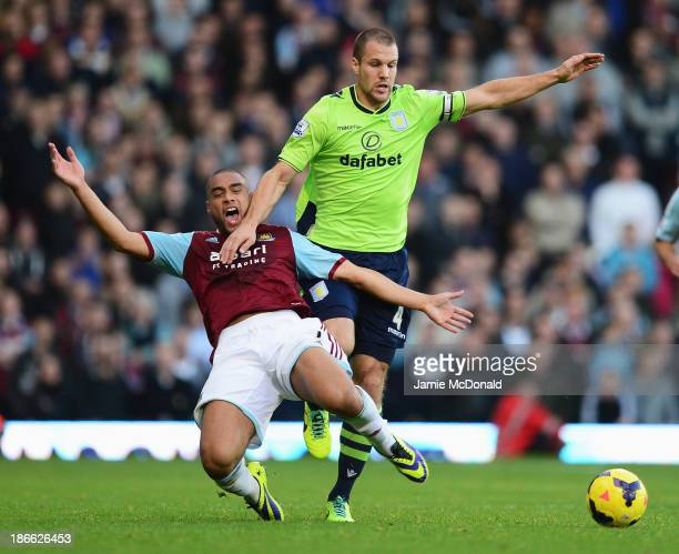 Ron Vlaar of Aston Villa challenges for the ball with Winston Reid of West Ham United during the Barclays Premier League match between West Ham...
