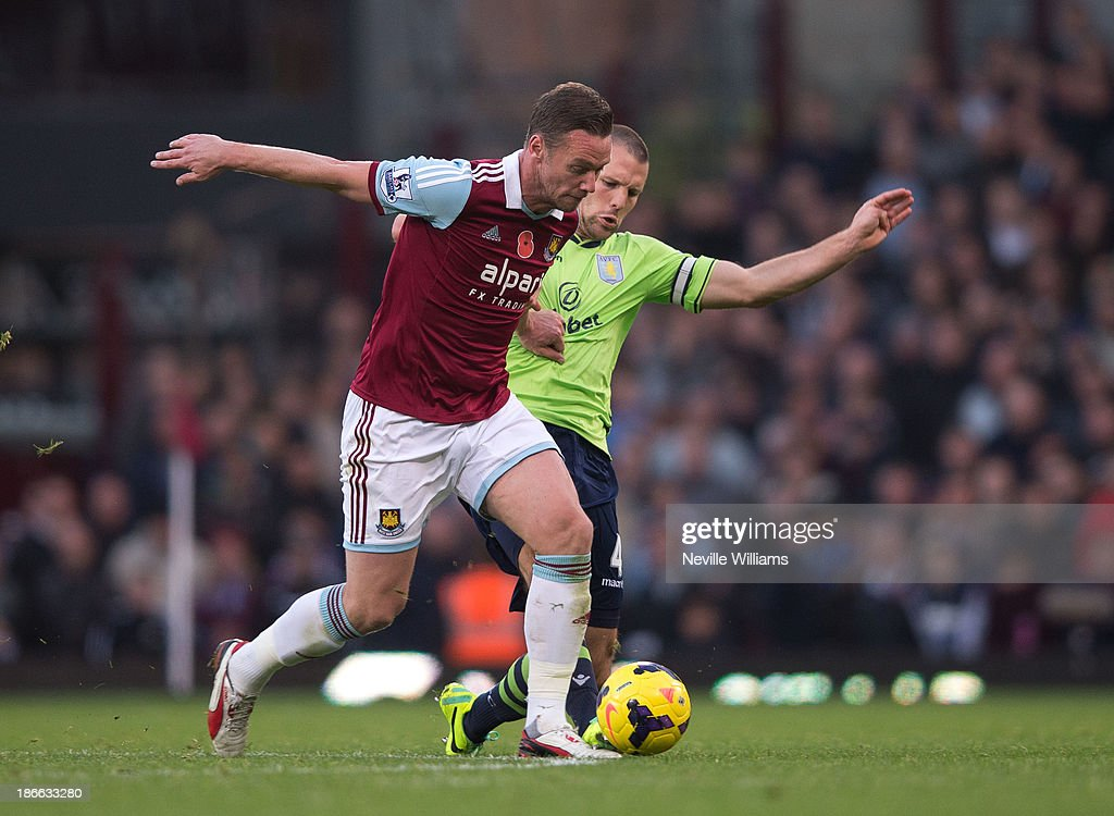 Ron Vlaar of Aston Villa is challenged by Kevin Nolan of West Ham United during the Barclays Premier League match between West Ham United and Aston Villa at the Boleyn Ground on November 02, 2013 in London, England.