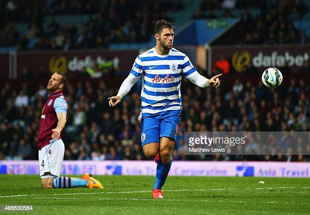 Ron Vlaar of Aston Villa look dejected as Charlie Austin of QPR celebrates as he scores their third goal during the Barclays Premier League match...