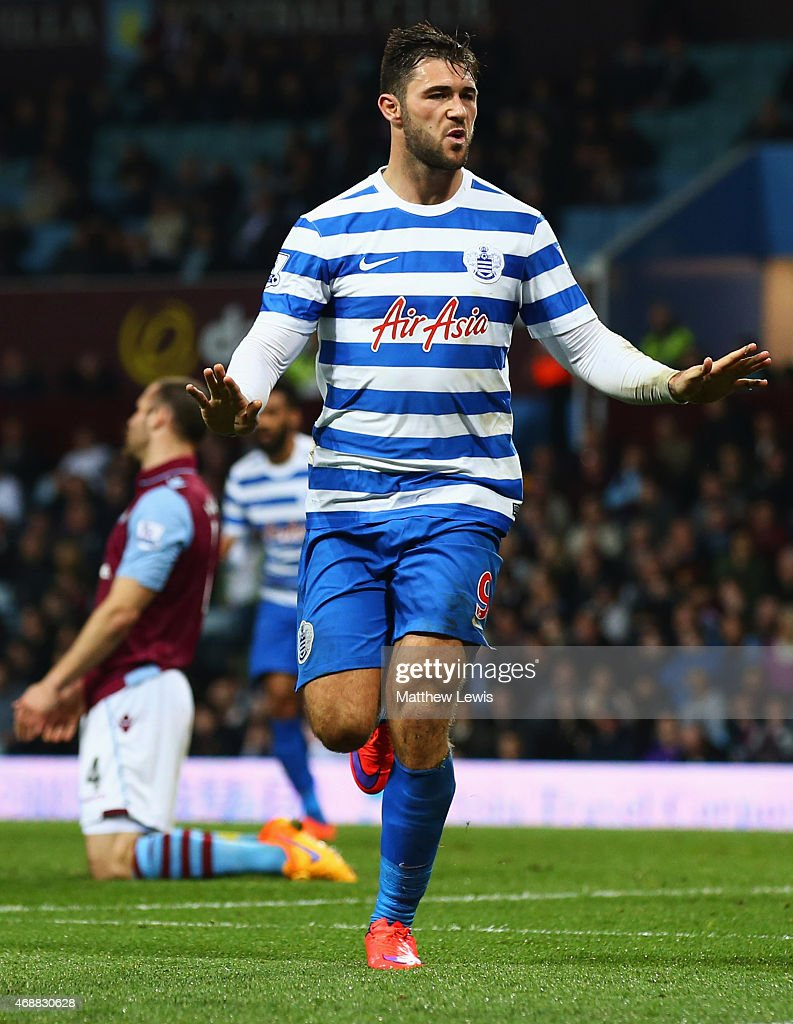 Ron Vlaar of Aston Villa (L) look dejected as Charlie Austin of QPR (9) celebrates as he scores their third goal during the Barclays Premier League match between Aston Villa and Queens Park Rangers at Villa Park on April 7, 2015 in Birmingham, England.