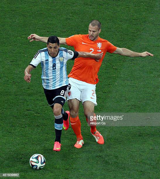 Ron Vlaar of Netherlands challenges Enzo Perez of Argentina during the 2014 FIFA World Cup Brazil Semi Final match between Netherlands and Argentina...