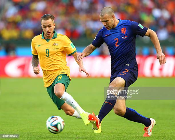 Ron Vlaar of the Netherlands controls the ball as Adam Taggart of Australia gives chase during the 2014 FIFA World Cup Brazil Group B match between...