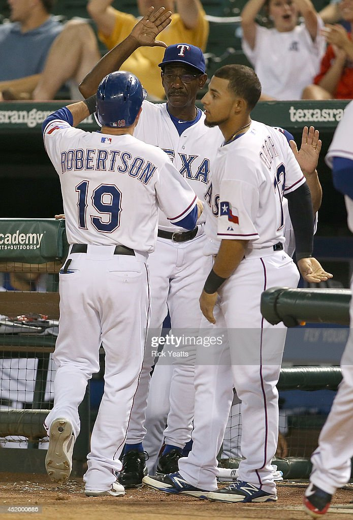 <a gi-track='captionPersonalityLinkClicked' href=/galleries/search?phrase=Ron+Washington&family=editorial&specificpeople=225012 ng-click='$event.stopPropagation()'>Ron Washington</a> manager #38 of the Texas Rangers and <a gi-track='captionPersonalityLinkClicked' href=/galleries/search?phrase=Rougned+Odor&family=editorial&specificpeople=12505074 ng-click='$event.stopPropagation()'>Rougned Odor</a> #73 congratulates Dan Robertson #19 of the Texas Rangers for scoring on a one run double hit by Jake Smolinski against the Los Angeles Angels of Anaheim at Globe Life Park in Arlington on July 10, 2014 in Arlington, Texas.