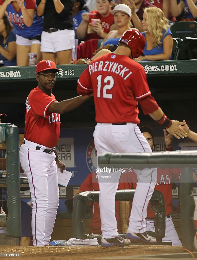 Ron Washington #38 manager of the Texas Rangers congratulates A.J. Pierzynski #12 for scoring in the sixth inning against the Houston Astros at Rangers Ballpark on September 23, 2013 in Arlington, Texas.