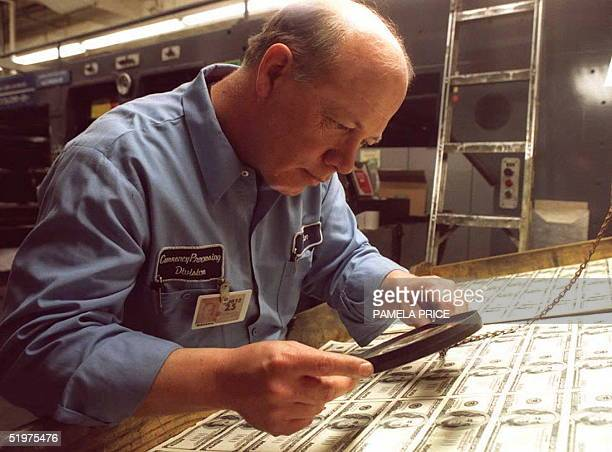 Ron Windsor an employee at the US Bureau of Engraving and Printing inspects a sheet of newly printed USD 100 bills 21 March before sending them to be...