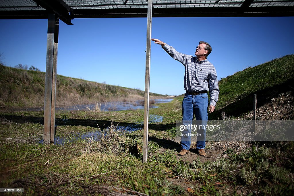 Ronald Gertson, a fourth generation rice farmer, shows where the level of water should be on a measuring stick in an irrigation canal as he deals with trying to grow rice during the severe drought on March 12, 2014 in Lissie, Texas. Recently the Texas Commission on Environmental Quality agreed to cut off water deliveries to most rice farmers in the Lower Colorado River Basin for the third straight year as the lakes in central Texas are only 38 percent full.