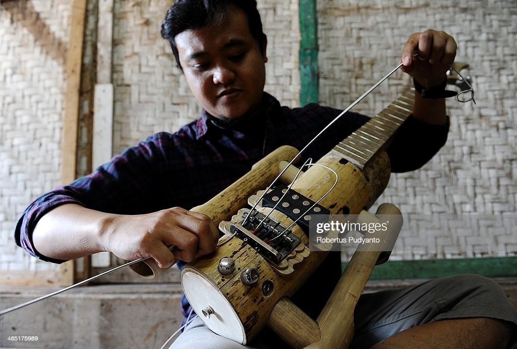 Ronald Harviana (28), a bamboo artisans puts strings on a bamboo guitar at his workshop in Tanjung Wangi Village on April 17, 2014 in Bandung, Java, Indonesia. Adang Muhidin, founder of Indonesian Bamboo Community, and his friends make sustainable bamboo musical instruments (guitar, violin, bass, trumpet, clarinet, saxophone, drums) a nod to the rise of the creative economy in Indonesia.