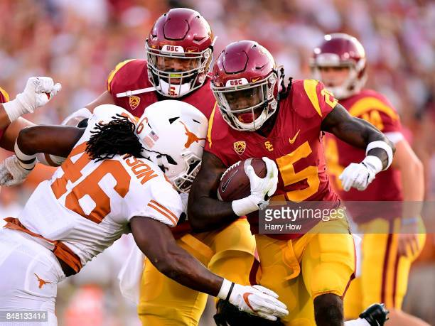 Ronald Jones II of the USC Trojans carries the ball as he is hit by Malik Jefferson of the Texas Longhorns during the first quarter at Los Angeles...