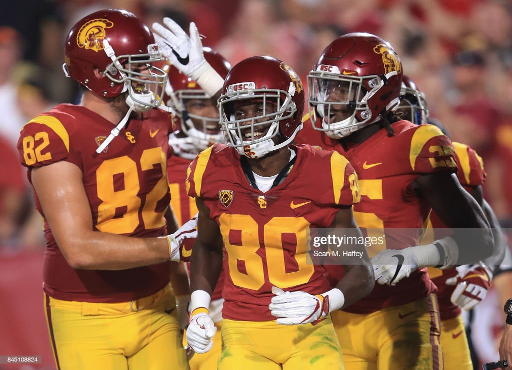 Ronald Jones II #25 of the USC Trojans (R) celebrates with Tyler Petite #82 and Deontay Burnett #80 after scoring a touchdown during the fourth quarter against the Stanford Cardinal at Los Angeles Memorial Coliseum on September 9, 2017 in Los Angeles, California.