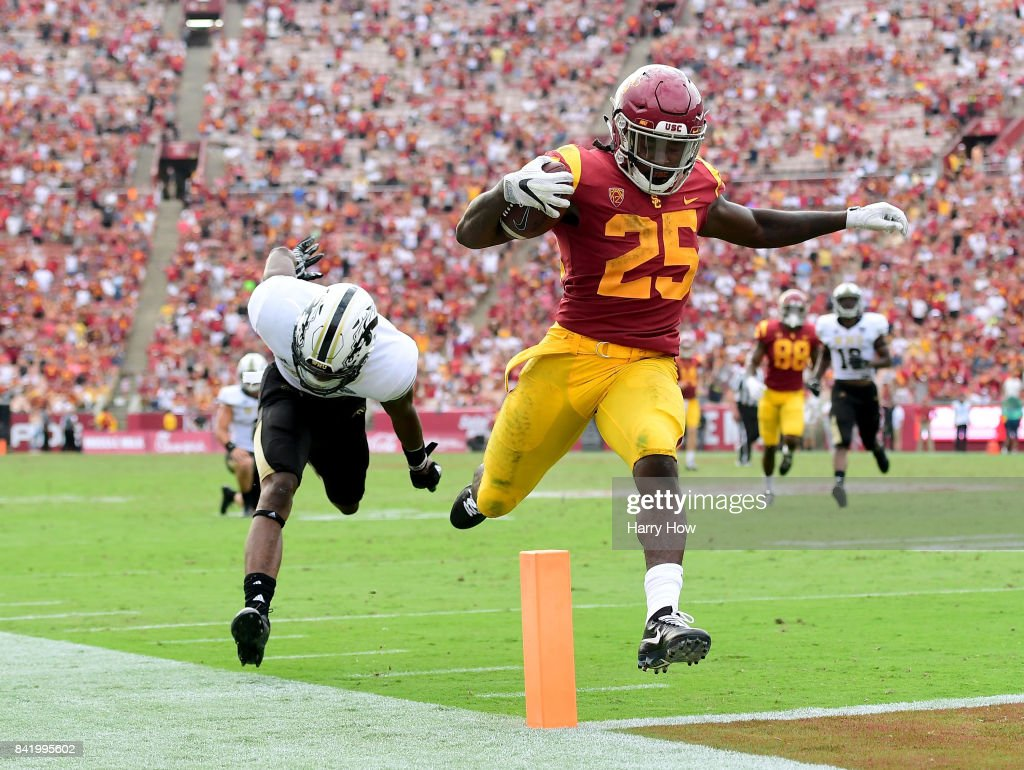 Ronald Jones II #25 of the USC Trojans scores a touchdown past Sam Beal #1 of the Western Michigan Broncos to take a 35-28 lead during the fourth quarter at Los Angeles Memorial Coliseum on September 2, 2017 in Los Angeles, California.