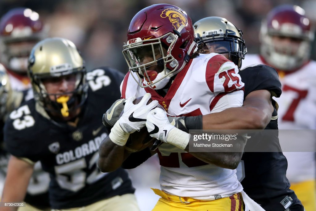 Ronald Jones II #25 of the USC Trojans tries to break free from Evan Worthington #6 of the Colorado Buffaloes at Folsom Field on November 11, 2017 in Boulder, Colorado.