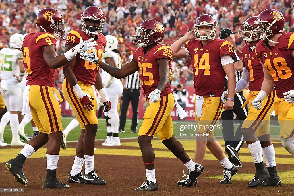 Ronald Jones #25 of the USC Trojans celebrates with teammate (left) JuJu Smith-Schuster #9 after scoring a touchdown in the first quarter against the Oregon Ducks at Los Angeles Memorial Coliseum on November 5, 2016 in Los Angeles, California.