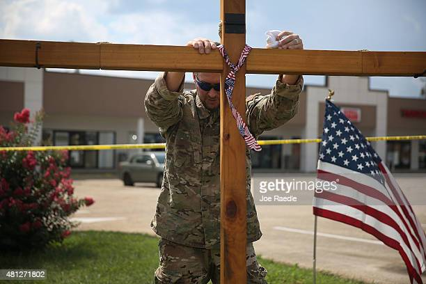 Ronald May prays as he supports a cross at a memorial setup in front of the Armed Forces Career Center/National Guard Recruitment Office which had...