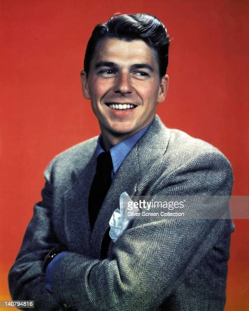 Ronald Reagan US actor wearing a grey herringbone jacket over a blue shirt and a black tie with his arms folded smiling in a studio portrait against...