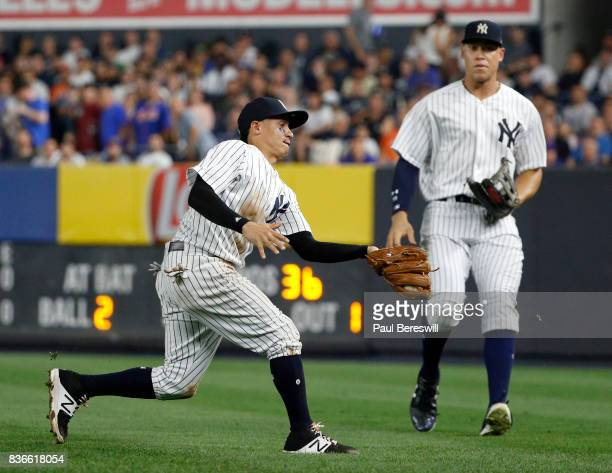 Ronald Torreyes of the New York Yankees catches a pop fly while running into the outfield in front of teammate Aaron Judge in an interleague MLB...