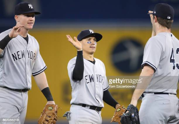 Ronald Torreyes of the New York Yankees celebrates their victory with Adam Warren and Garrett Cooper during MLB game action against the Toronto Blue...