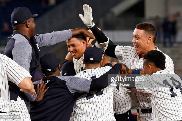 Ronald Torreyes of the New York Yankees celebrates with teammates after hitting a walk off single against the Texas Rangers during the tenth inning...