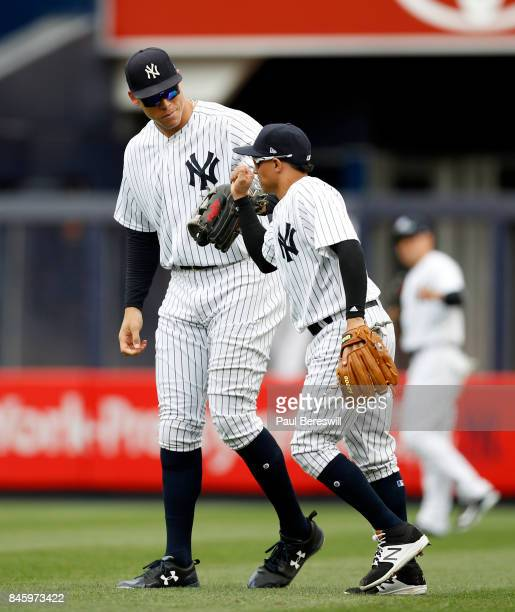 Ronald Torreyes of the New York Yankees gets congratulated on a nice play by Aaron Judge of the New York Yankees who towers over him in an MLB...