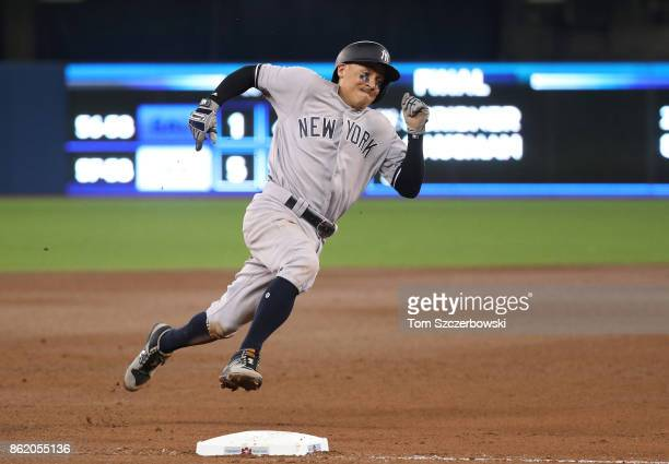Ronald Torreyes of the New York Yankees rounds third base and heads for home plate as he tries to score before being thrown out at home in the eighth...