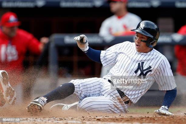 Ronald Torreyes of the New York Yankees scores a run on a fielders choice during the sixth inning against the St Louis Cardinals at Yankee Stadium on...