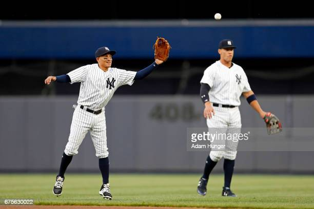 Ronald Torreyes of the New York Yankees warms up next to Aaron Judge of the New York Yankees prior to taking on the Baltimore Orioles at Yankee...