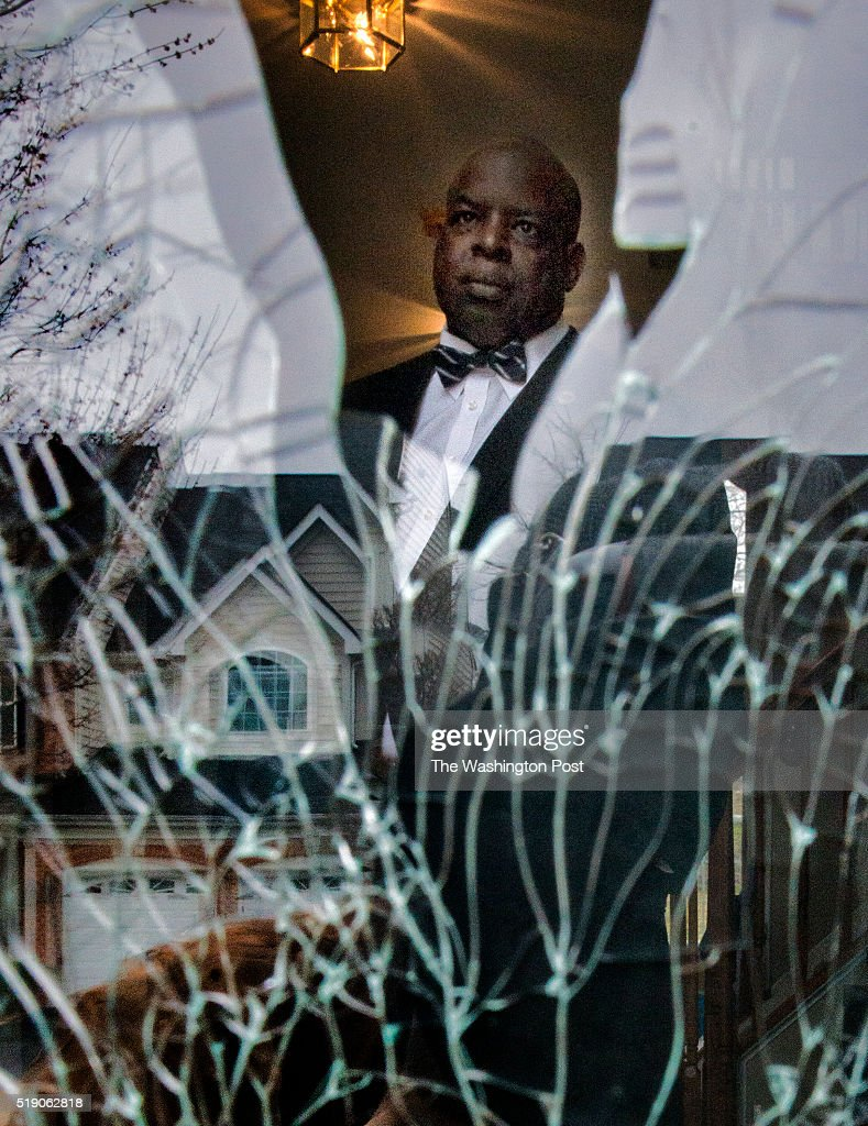 Ronald W Hamilton behind the shattered glass of the front door of the house where his son shot and killed his daughter in law and a police officer...