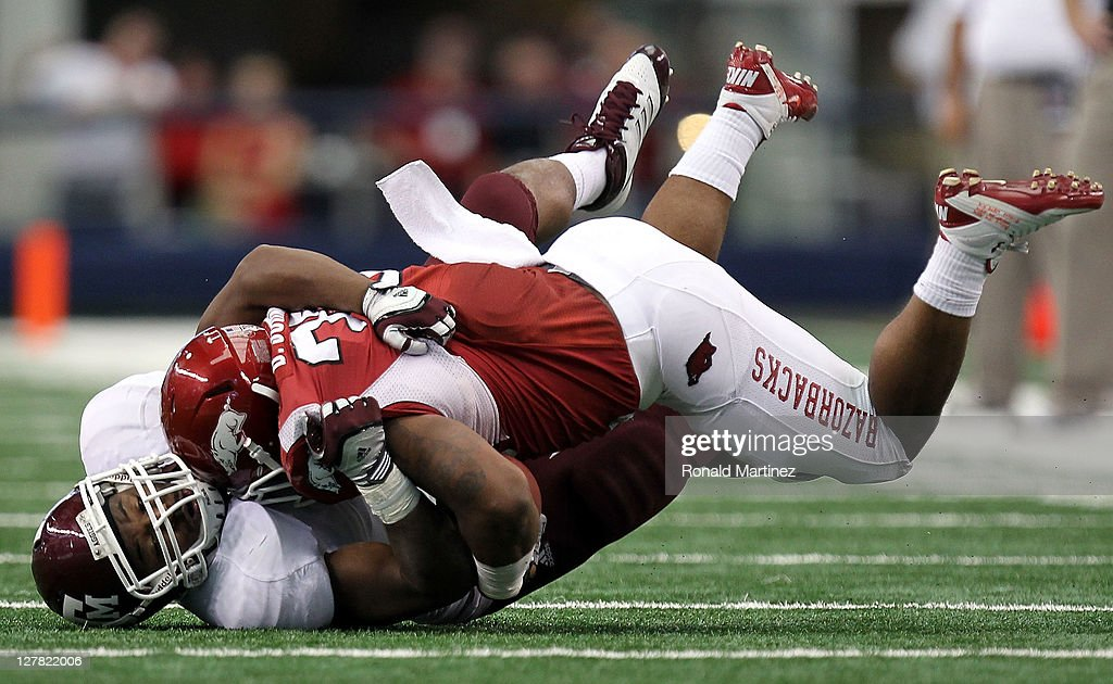 Ronald Watkins #30 of the Arkansas Razorbacks is tackled by Charlie Thomas #9 of the Texas A&M Aggies at Cowboys Stadium on October 1, 2011 in Arlington, Texas.