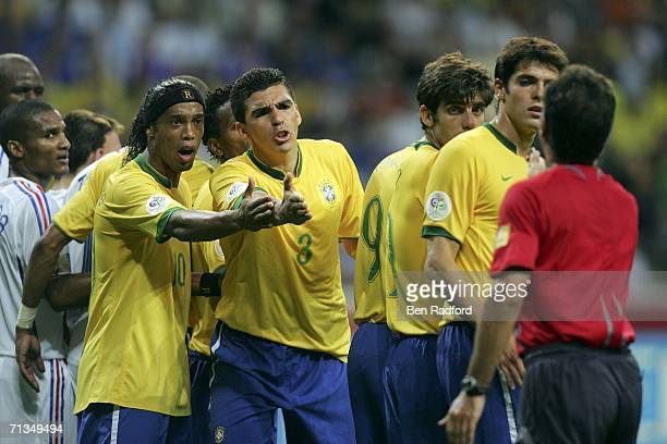 Ronaldinho and Lucio of Brazil argue with Referee Luis Medina Cantalejo of Spain after being told to move their defensive wall backwards during the...