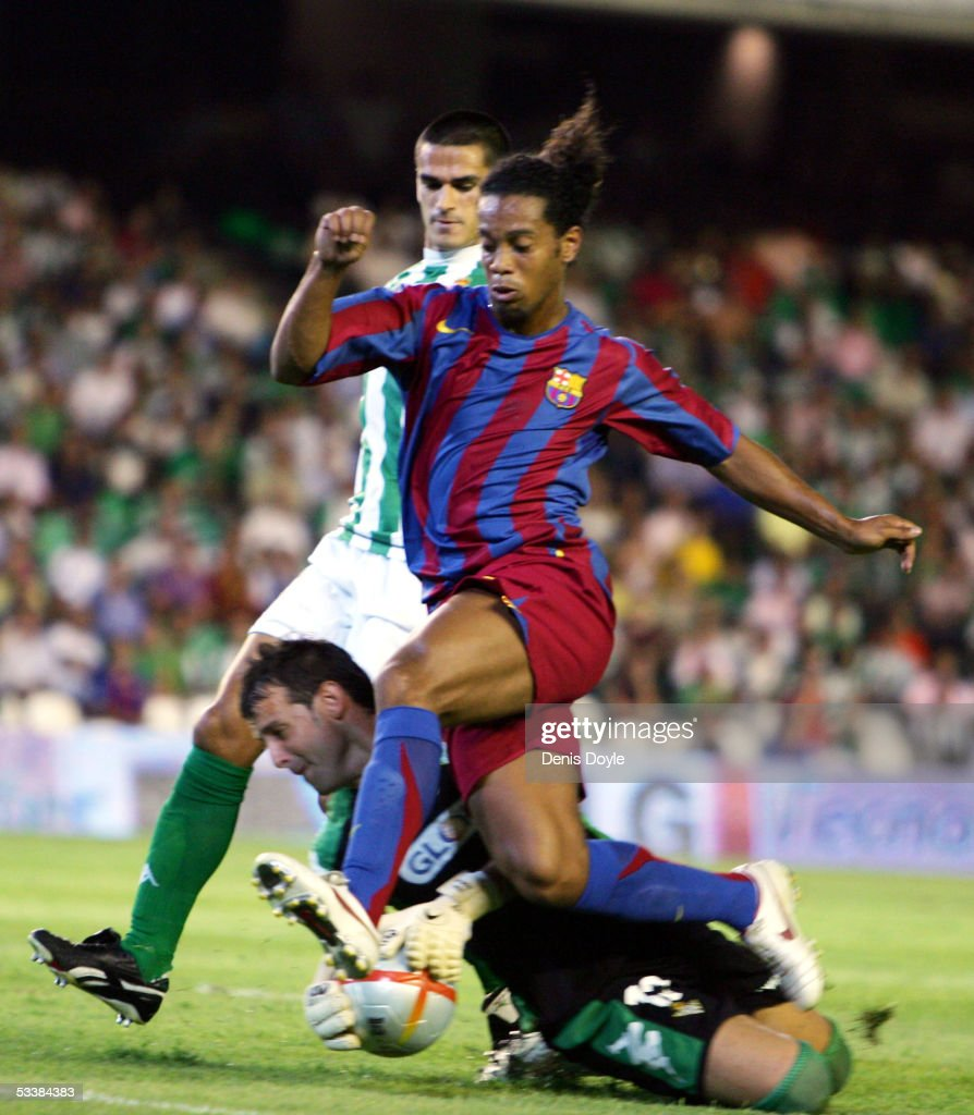 Ronaldinho of Barcelona is tackled by Betis goalkeeper Doblas during a Supercup first leg match between Real Betis and FC Barcelona at the Ruiz de...