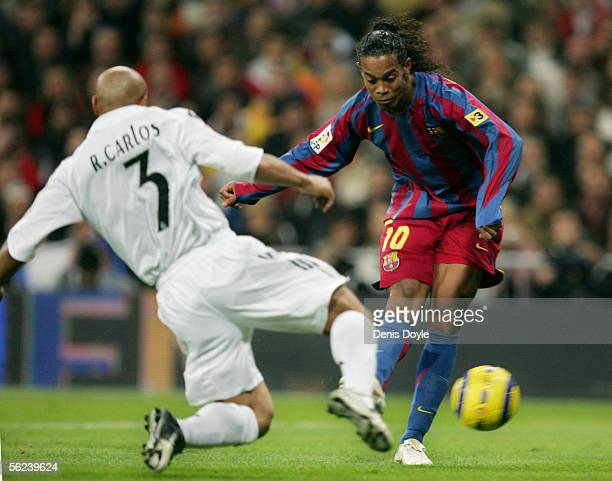 Ronaldinho of Barcelona shoots the ball past Roberto Carlos to score a goal during a Primera Liga match between Real Madrid and FC Barcelona at the...