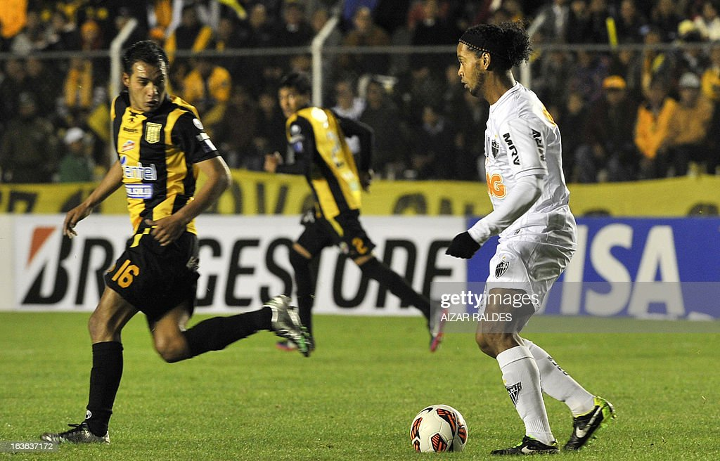 Ronaldinho (R) of Brazil's Atletico Mineiro is marked by Diego Bejarano of Bolivia's The Strongest during their Copa Libertadores football match at Hernando Siles stadium in La Paz, Bolivia, on March 13, 2013. AFP PHOTO/Aizar Raldes