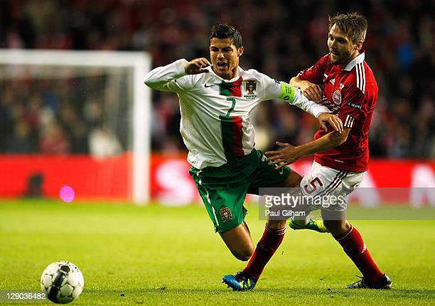 Ronaldo of Portugal is tackled by Michael Silberbauer of Denmark during the EURO 2012 group H qualifier match between Denmark and Portugal at Parken...