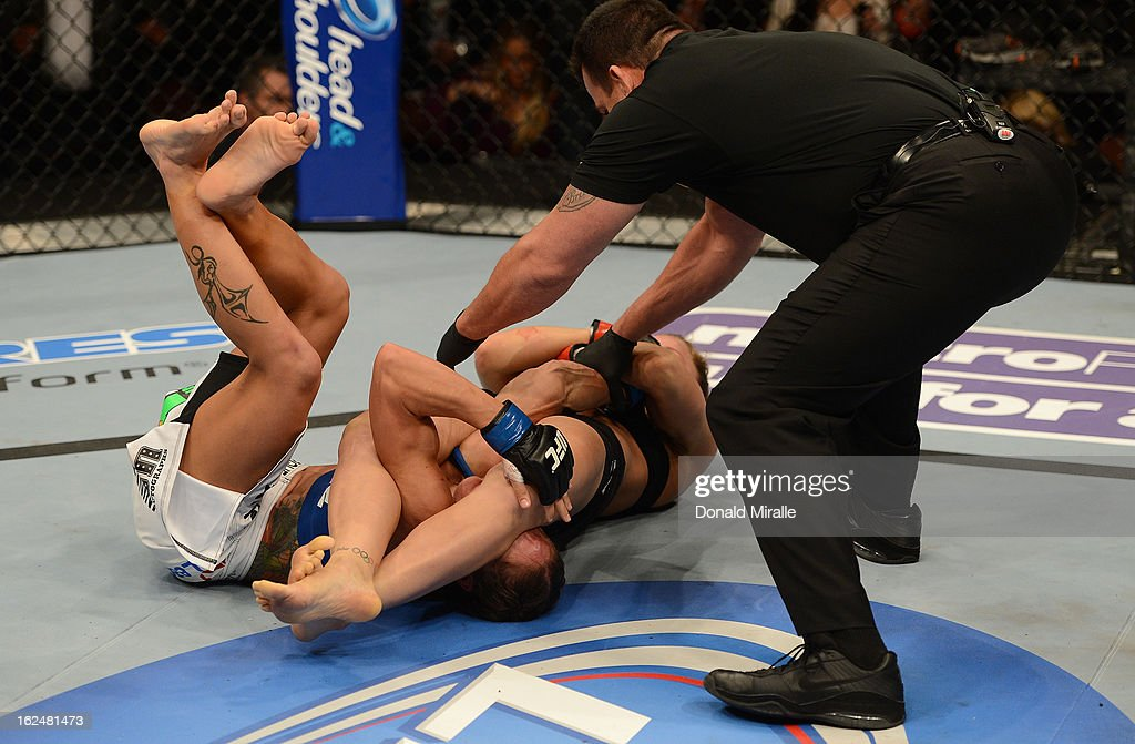 Ronda Rousey (center) attempts to submit Liz Carmouche in their women's bantamweight title fight during UFC 157 at Honda Center on February 23, 2013 in Anaheim, California.
