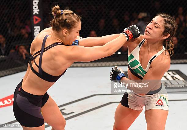 Ronda Rousey of the United States punches Bethe Correia of Brazil in their UFC women's bantamweight championship bout during the UFC 190 event inside...