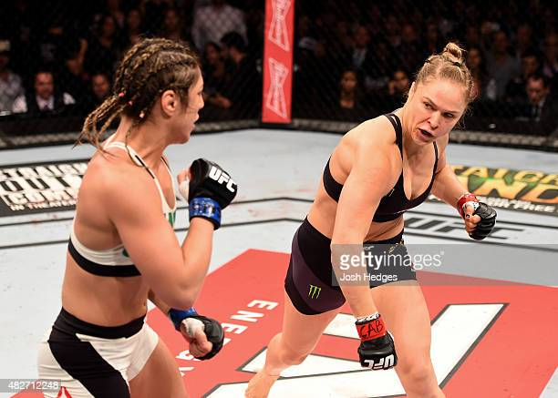 Ronda Rousey of the United States throws a punch at Bethe Correia of Brazil in their UFC women's bantamweight championship bout during the UFC 190...