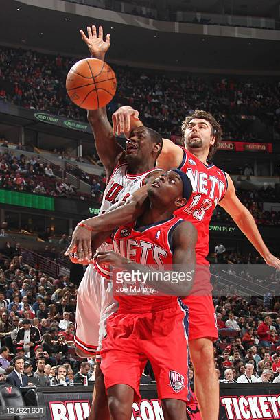 Ronnie Brewer of the Chicago Bulls battles for a rebound with Anthony Morrow and Mehmet Okur of the New Jersey Nets during the NBA game on January 23...