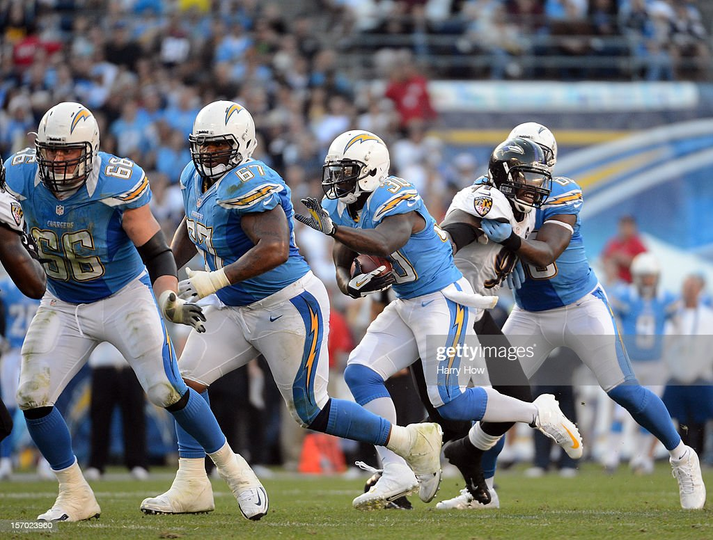 Ronnie Brown #30 of the San Diego Chargers looks for a block from Rex Hadnot #67 and Jeromey Clary #66 during a 16-13 loss to the Baltimore Ravens at Qualcomm Stadium on November 25, 2012 in San Diego, California.