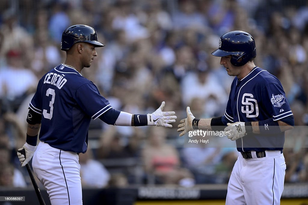 Ronnie Cedeno congratulates Chris Denorfia of the San Diego Padres after scoring a run in the game against the Colorado Rockies at Petco Park on...