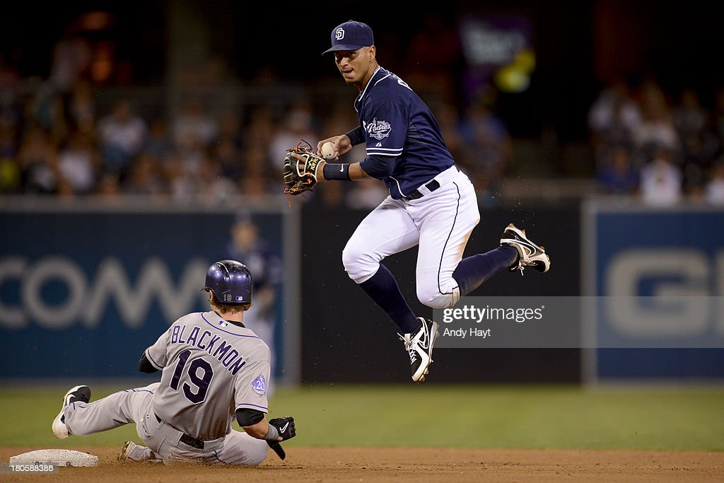 Ronnie Cedeno of the San Diego Padres attempts a double play at second base against Charlie Blackmon of the Colorado Rockies at Petco Park on...